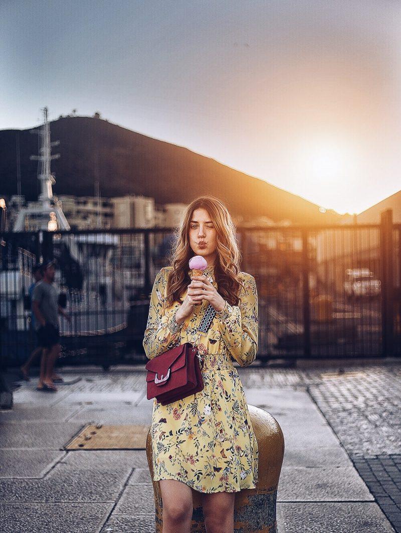Gelbes Blumenkleid und eine Tasche von Coccinelle, Sonnenuntergang an der Waterfront Kapstadt
